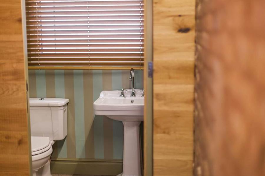 Puerta de aseo integrada en panelado mismo plano. Cara interior lacado blanco